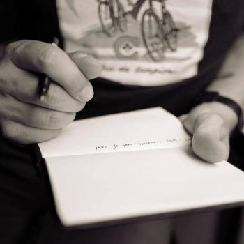 a photo of hands holding a notebook and a pen
