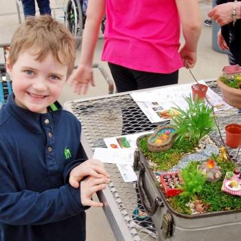Child posing with his mini-garden