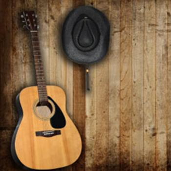 Guitar and black cowboy hat on wooden plank wall