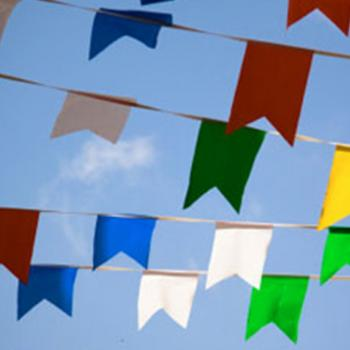 Brightly colored flags against clouds in a sunny sky