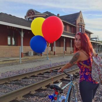 Woman with balloons in front of old building