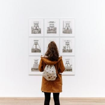 A photo of a person looking at art on a gallery wall