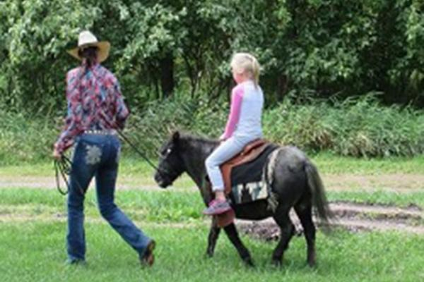cowgirl giving a child a ride on a small horse